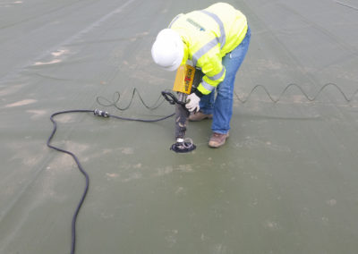 Plate being installed onto geomembrane cover