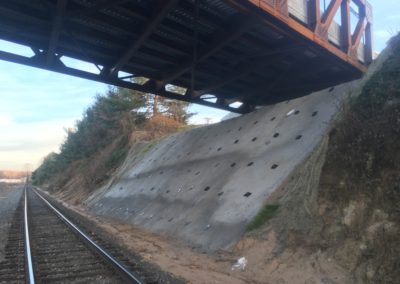 concrete face over anchored slope next to rail line