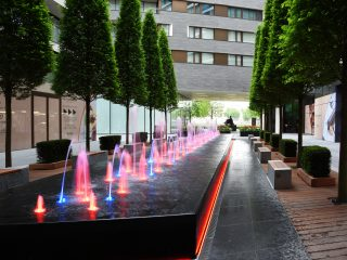Trees & fountains in outdoor courtyard of One Tower Bridge in London, UK
